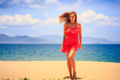 Blond girl in red stands on sand wind shakes long hair. Blond slim girl in short red frock stands barefoot on sand beach against azure sea wind shakes long hair royalty free stock images