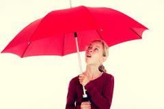 Blond girl with red umbrella. In frontof white background Stock Photos