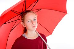 Blond girl with red umbrella. In frontof white background Stock Photo