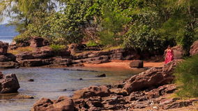 Blond Girl in Red Walks by Rocks along Beach with Plants. Blond girl in long red frock walks on sand beach near rocks in shallow water against tropical plants stock footage