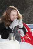 Blond girl relaxing in a snowy park. Smiling blond girl in winther cloths sitting on a bench in winter snowy park Royalty Free Stock Photo