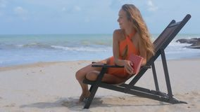 Blond Girl Rests in Folding Chair on Ocean Beach. Blond girl with long loose flowing hair rests in folding chair on empty sand beach against ocean waves stock footage