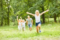 Blond girl is running over a meadow stock image