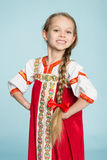 Blond girl in the Russian folk costume. Blond girl with a scythe in the traditional Russian folk costume. Girl seven years royalty free stock photo