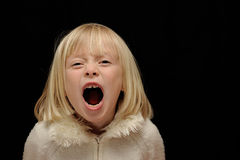 Blond Girl Screaming. Young blond girl shown screaming against a black background.  Right side left for copy Royalty Free Stock Images