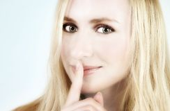 Blond girl with a secret Royalty Free Stock Images