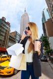 Blond girl shopaholic talking phone fifth avenue NY Stock Photography