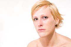 Blond girl with short hair who is feeling sad. Studio portrait of a sad looking short haired blond girl stock photo