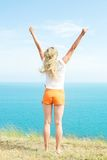 Blond girl in shorts. Is raising his hands up against the blue of the sea Stock Photos