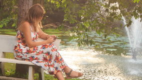 Blond Girl Sits on Bench by Fountain Checks Phone in Park stock video footage