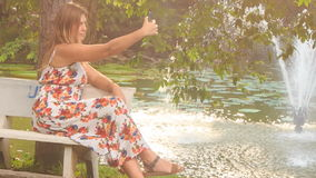 Blond Girl Sits on Bench by Fountain Makes Selfie in Park. Blond girl in colorful frock sits on bench near pond with fountain in park and makes selfie with stock footage