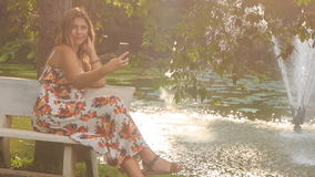 Blond Girl Sits on Bench at Fountain Waves Hand in Park. Blond girl in colorful frock sits on bench near pond with fountain in park waves hand checks iphone at stock footage