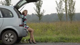 Blond girl sits in open trunk of her broken car with blinking emergency signal on a country road stock video