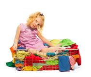 Blond girl sitting in the basket with clothes Stock Photos