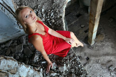 Blond girl sitting on edge in abandoned building Royalty Free Stock Photography