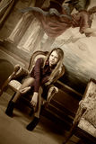 Blond girl  sitting on a luxury armchair Royalty Free Stock Images