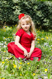 Blond girl sitting in meadow Stock Photography