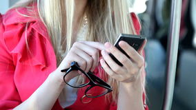 Blond girl sitting in tram, close up on mobile, phone, cell, holding glasses stock video footage