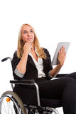 Blond girl sitting in a wheel chair. With tablet PC Royalty Free Stock Images