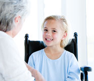 Blond girl sitting on a wheelchair. Blond little girl sitting on a wheelchair talking with her grandmother in a hospital Royalty Free Stock Image