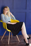 Blond girl in skirt and vest sits on a chair Royalty Free Stock Photos
