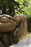 Blond girl sleeping. Outdoor portrait of a blond girl sleeping on a branch tree in a park Royalty Free Stock Photos