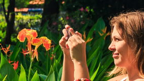 Blond Girl Smells at Tropical Flower Takes Photo in Park. European blond girl smells beautiful tropical flower and takes photo of it in park stock footage