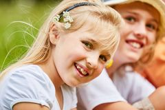 Blond girl smiles mischievously. Blond girl with flowers in her hair smiles mischievously and curiously stock photos