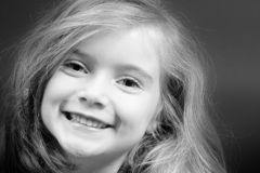 Blond girl smiling  in black and white. Cute blond girl with strong eye-contact and big smile Royalty Free Stock Photography