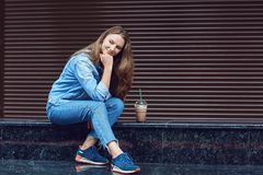 Blond girl smiling sitting with cocktail in plastic cup.  royalty free stock photos