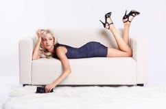 Blond girl on sofa Stock Image