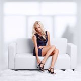 Blond girl on sofa. Full-length portrait of beautiful young blond woman on couch checking court shoe fastener royalty free stock photo