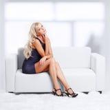 Blond girl on sofa Stock Photography