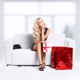 Blond girl on sofa. Full-length portrait of beautiful young blond woman on couch with shopping bags and gift in hands Stock Photos