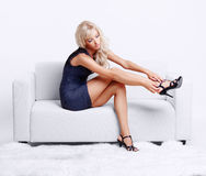 Blond girl on sofa. Full-length portrait of beautiful young blond woman on couch checking court shoe fastener royalty free stock photos