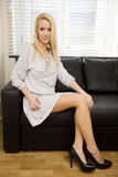 Blond girl on a sofa Royalty Free Stock Photos