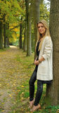 Blond girl standing against tree. Attractive blond girl standing against tree in the woods royalty free stock image