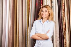 Blond girl standing in fabric store. Royalty Free Stock Photo