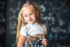 Blond girl standing near a black slate with a pile of books. Free space. Black background. School concept stock image