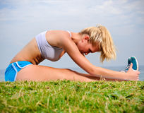 Blond girl stretches Stock Images