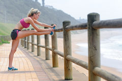 Blond girl stretches hamstrings Royalty Free Stock Photos