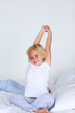 Blond girl stretching in bed Royalty Free Stock Images