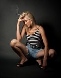 Blond girl in stripped shirt smoking cigarette Stock Image