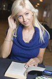 Blond girl studying. Beautiful blond girl is studying in library stock photography
