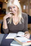 Blond girl studying. Gazing at the camera royalty free stock images