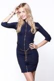 Blond girl styling a luxury zip dress Stock Photography