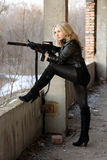 Blond girl with submachine gun. Blond girl on high heels taking a shot with machine gun royalty free stock photography
