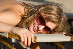 Blond girl sunbathing on a lounge Royalty Free Stock Images