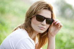 Blond girl in sunglasses at the summer park. Royalty Free Stock Images
