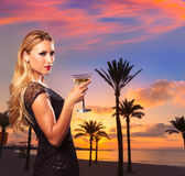 Blond girl sunset Arenal beach drinking vermout Royalty Free Stock Image